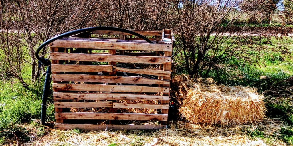 An image of the first wooden pallet composting bin built by Marlon & Alexia. One more way to compost everything